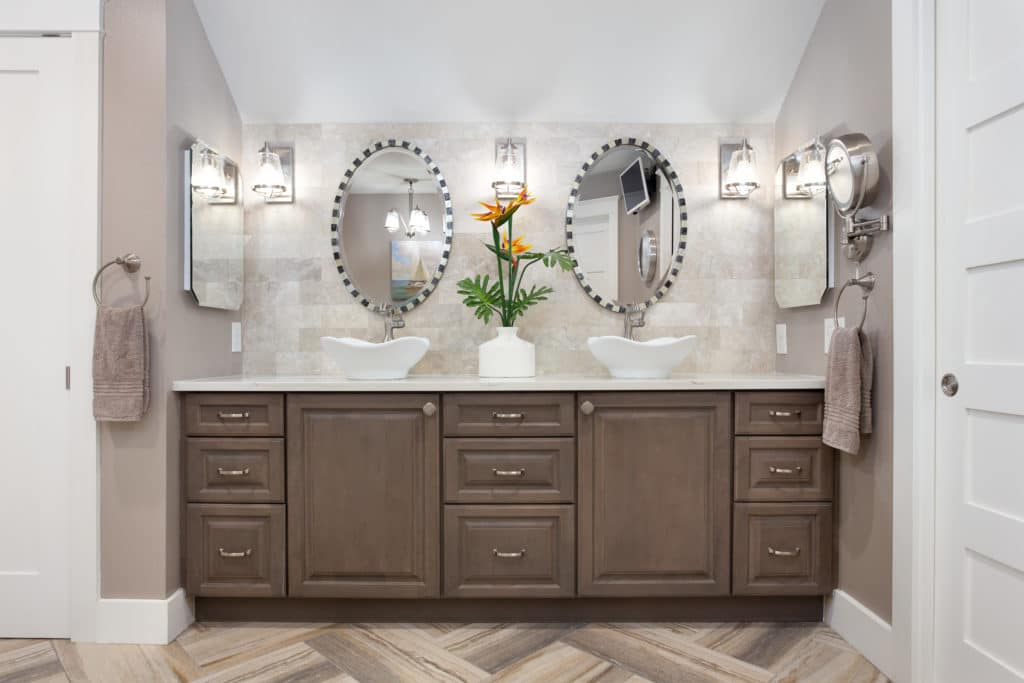 Bathroom decor includes coastal, shabby chic master bathroom has warm, weathered gray cabinets with tulip white vessel sinks all set against a backdrop of stone tile.