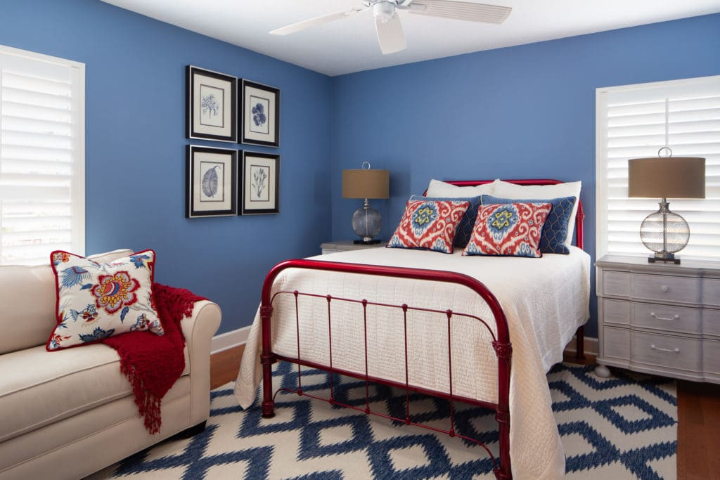 Bedroom decor includes custom pillows in shades of blue and red to compliment this vintage iron bed painted in a cherry red finish.
