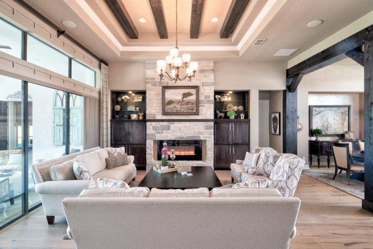 Interior design includes this rustic, modern great room featuring a stone fireplace and built-in cabinetry. Rustic wood beams balance modern custom drapes and furnishings.