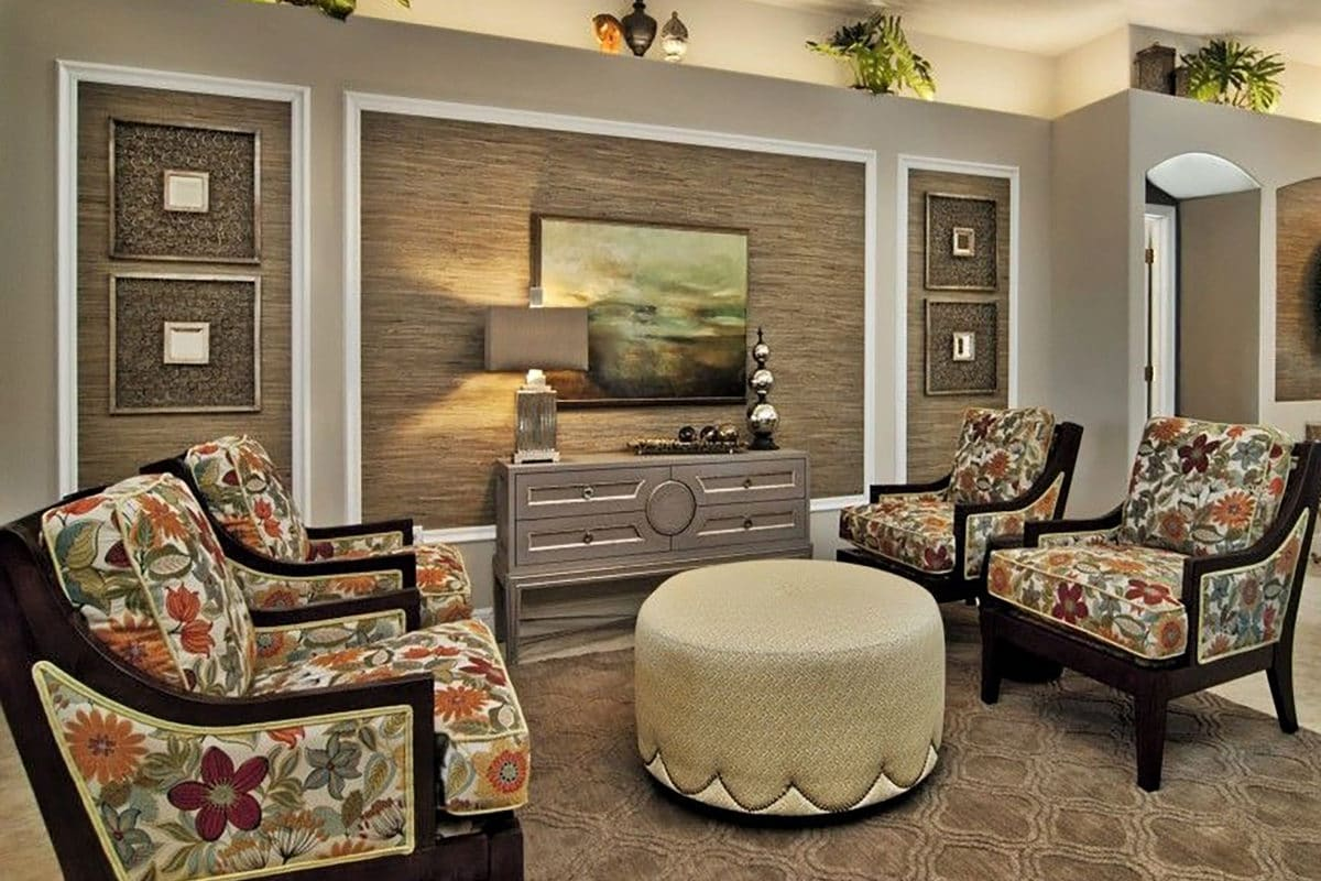 This living room decor was enhanced with wood molding and grasscloth. creating a design style with a mix of modern and tropical