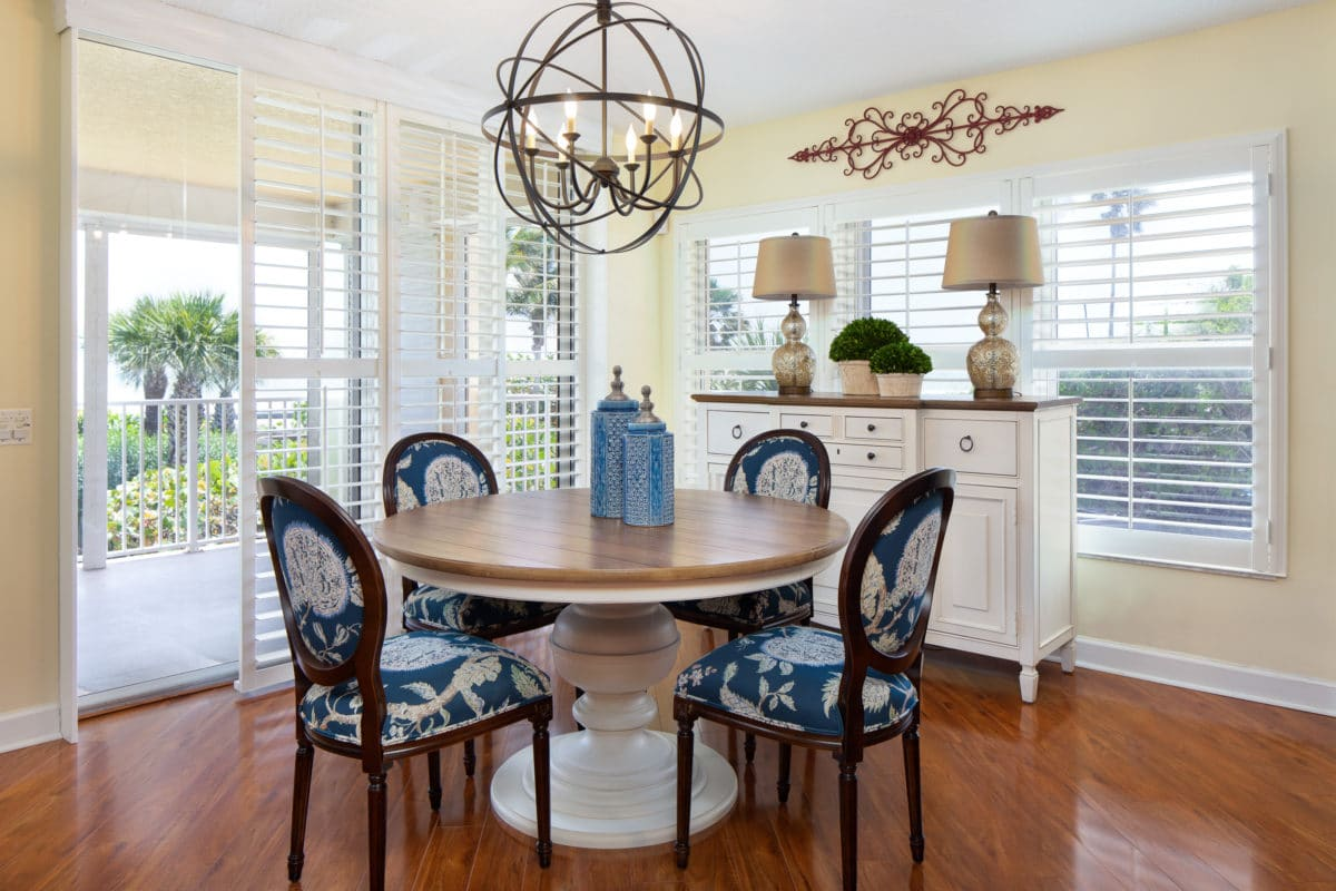 Plantation shutters are the perfect solution for this dining room with both sliding doors and a large window.